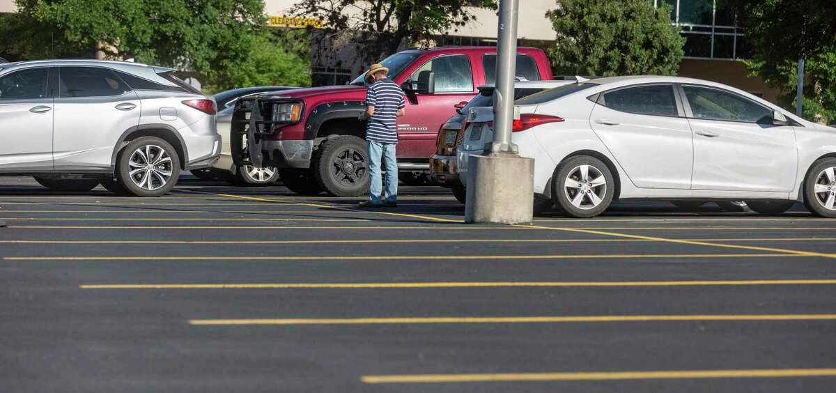 A patient waits outside the UT Health San Antonio MD Anderson Cancer Center, where patients needing treatment now wait in a parking lot instead of a waiting room.