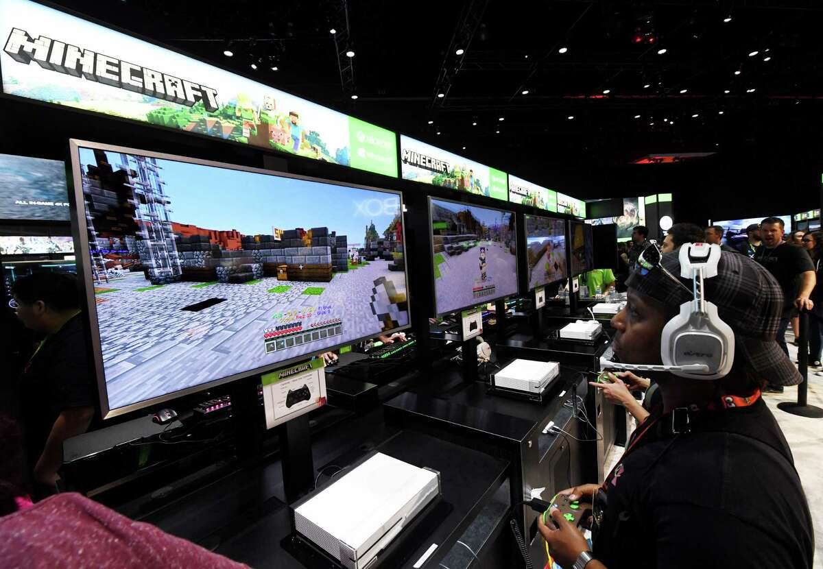 """Gamers in the Microsoft Xbox exhibit play the """"Minecraft"""" game at the Los Angeles Convention center on day one of E3 2017, the three day Electronic Entertainment Expo, one of the biggest events in the gaming industry calendar, in Los Angeles, California on June 13, 2017. / AFP PHOTO / Mark RALSTONMARK RALSTON/AFP/Getty Images"""
