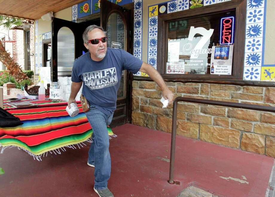 John Gerhart tosses a free roll of toilet paper he was given to his wife as part of his to-go order at 7 Leguas Mexican Restaurant, Friday, April 10, 2020, in Montgomery. Photo: Jason Fochtman, Houston Chronicle / Staff Photographer / 2020 © Houston Chronicle
