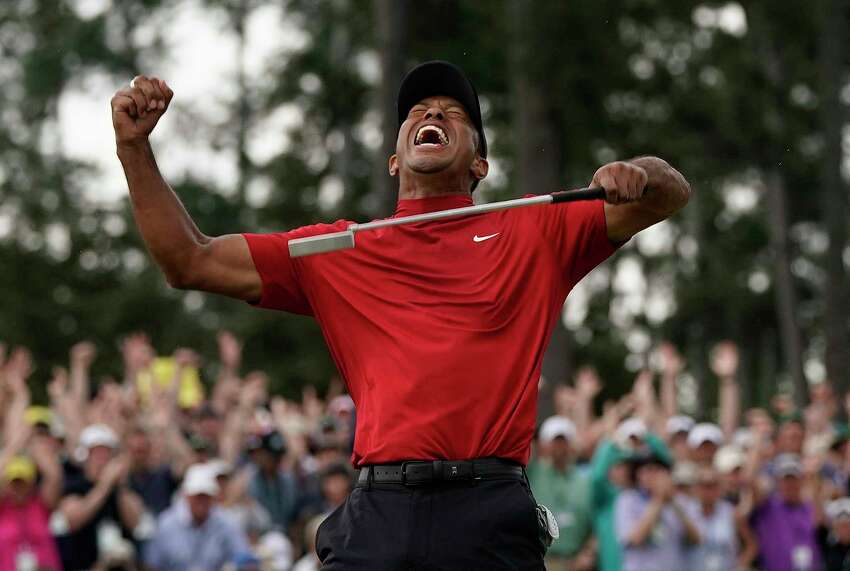 FILE - In this April 14, 2019, file photo, Tiger Woods reacts as he wins the Masters golf tournament at Augusta National in Augusta, Ga. It was voted the third best Masters. Woods blazing to victory in his Sunday red at the Masters, a scene once so familiar, was never more stunning. (AP Photo/David J. Phillip, File)