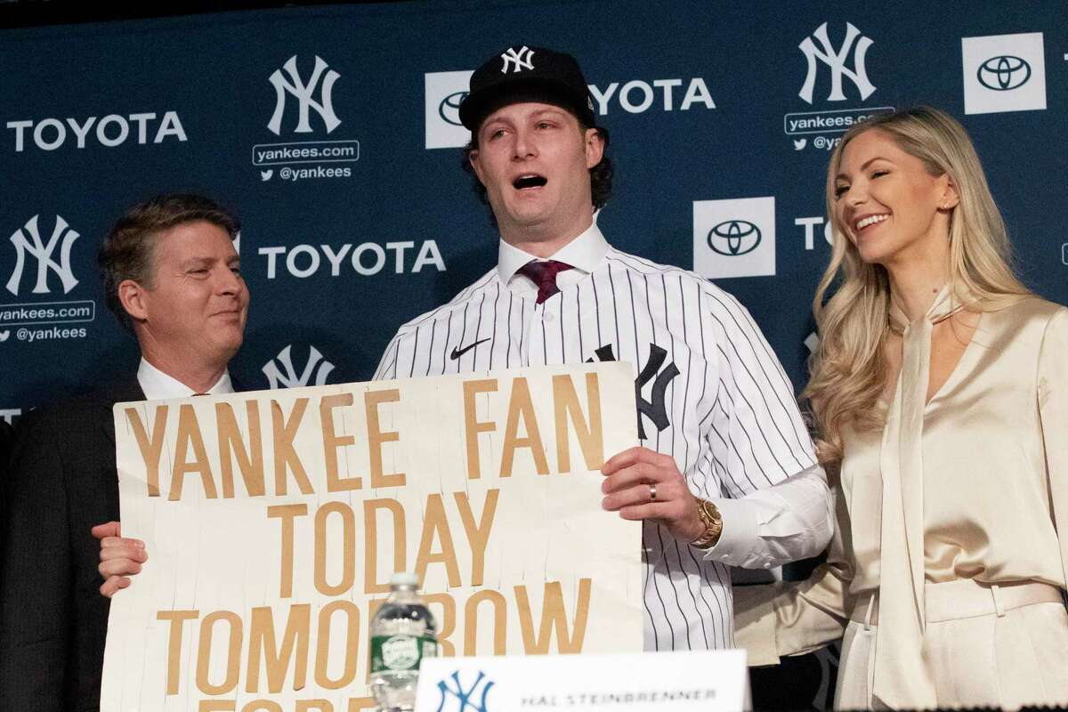 New York Yankees pitcher Gerrit Cole, center, holds a sign he used as a young Yankees fan, as he is introduced as the baseball clubs newest player during a baseball media availability, Wednesday, Dec. 18, 2019 in New York. He is joined by team owner Hal Steinbrenner, left, and his wife, Amy Cole. The Coles purchased a home in Greenwich.