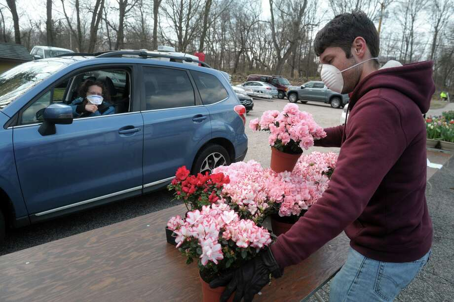 Aaron Egensteiner of the White Hills Volunteer Fire Company helps a woman as she picks out flowers during the annual Easter Flower Sale in Shelton, Conn. April 4, 2020. Due to coronavirus precautions, this year's sale relied of orders made online for home delivery, as well as the drive-thru pickup selections available behind the firehouse on School Street. Photo: Ned Gerard / Hearst Connecticut Media / Connecticut Post