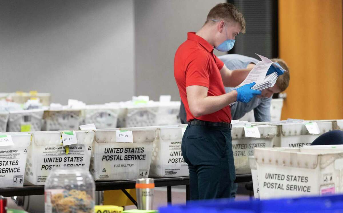 A City of Milwaukee Election Commission worker processes and sorts absentee ballots for Tuesday's primary election, Wednesday, April 8, 2020, in downtown Milwaukee, Wis. (Mark Hoffman/Milwaukee Journal-Sentinel via AP)