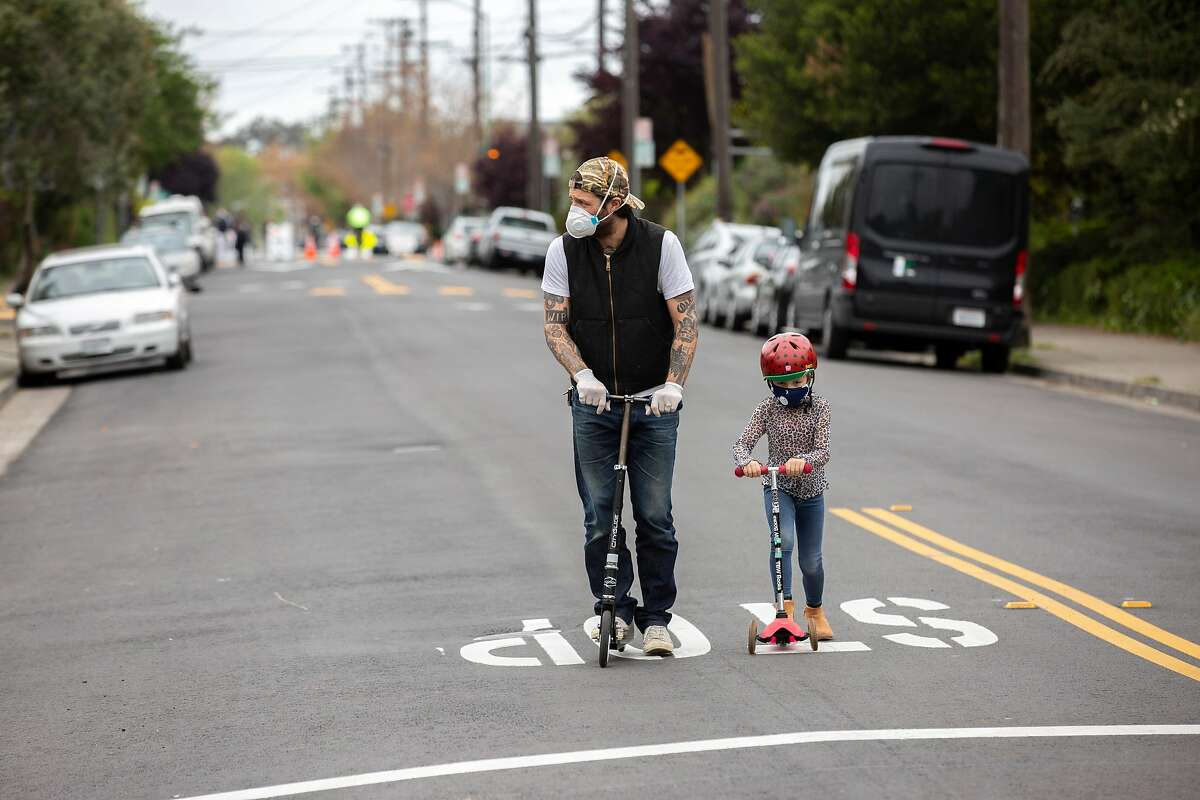 From left: Paul Schiek and his daughter Rosary Schiek, 6, ride scooters along 42nd Street on Saturday, April 11, 2020, in Oakland, Calif. Mayor Libby Schaaf ordered approximately 10% of Oakland streets too close. It's about 74 miles of roadway. The purpose is for people to walk, jog or ride bicycles during the shelter-in-place period. The closures are happening in phases. Crews will put temporary plastic barriers on the first batch of streets Saturday, allowing enough space for people who live on the affected streets to drive to and from their homes.