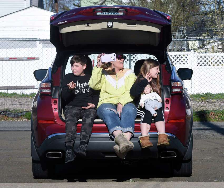 From left, Jacaob Verespej, 10, his mother, Lori and sister, Juliana, 9, with her doll, Posie, watch the