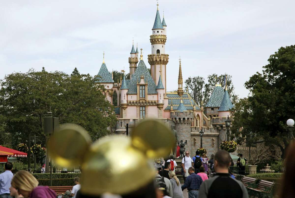 FILE - In this file photo, visitors walk toward Sleeping Beauty's Castle in the background at Disneyland Resort in Anaheim.