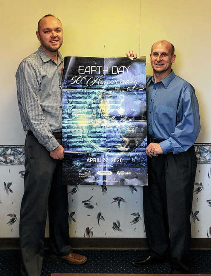 Michael Bellovich and Mike E. Spann display Country Financial's Agriculture in the Classroom Earth Day posters. Photo: Photo Provided