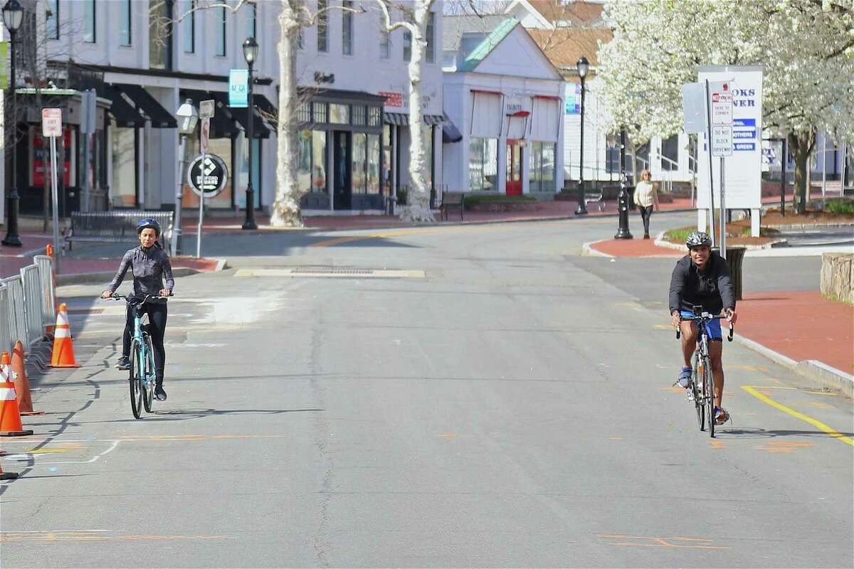 Two bikers keep their distance from one another on Main Street on Saturday afternoon, April 11, 2020, in Westport, Conn.