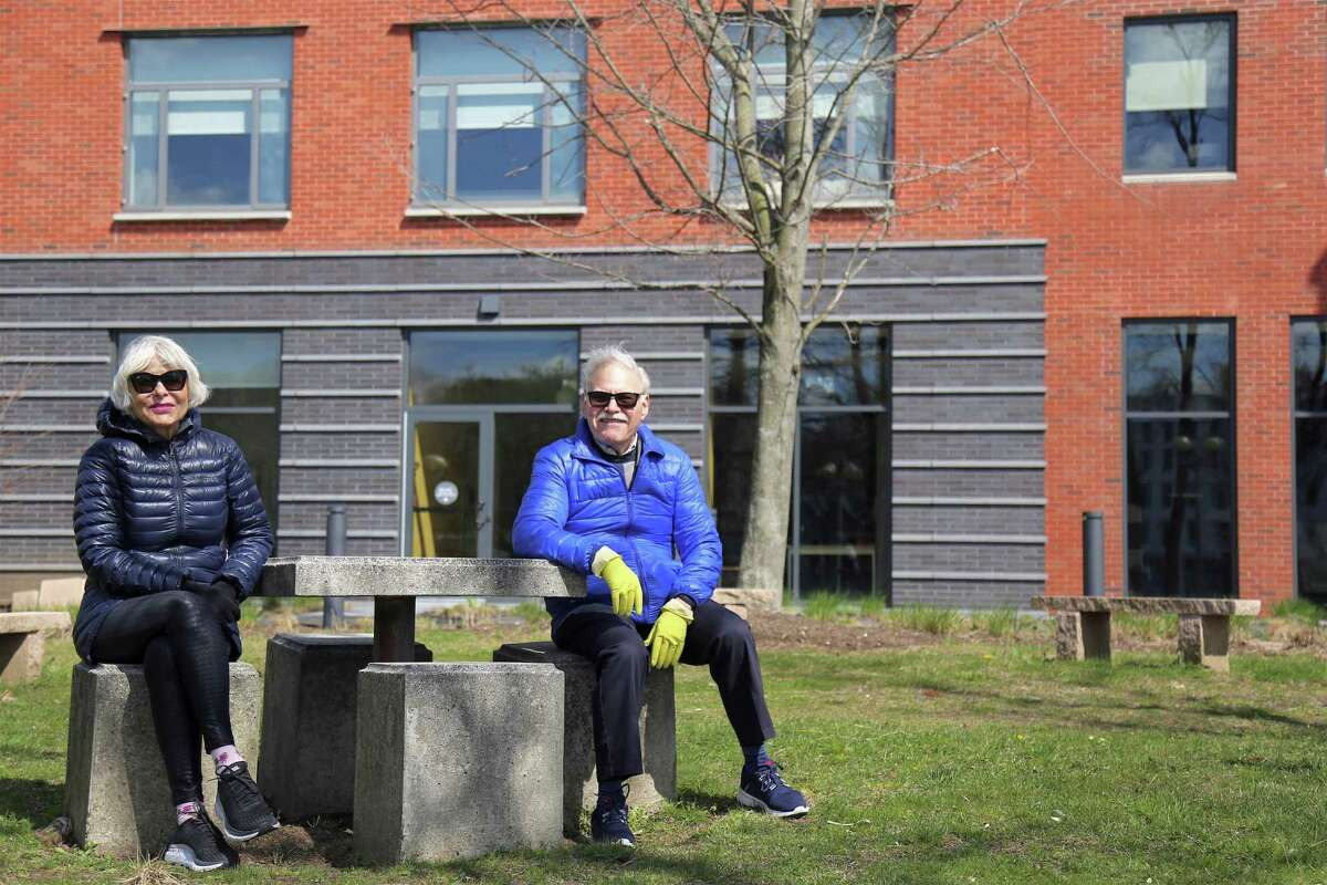 Sandra Benee of Greenwich and Bernard Simpkin of New Canaan enjoy the view from the library lawn on Saturday afternoon, April 11, 2020, in Westport, Conn.