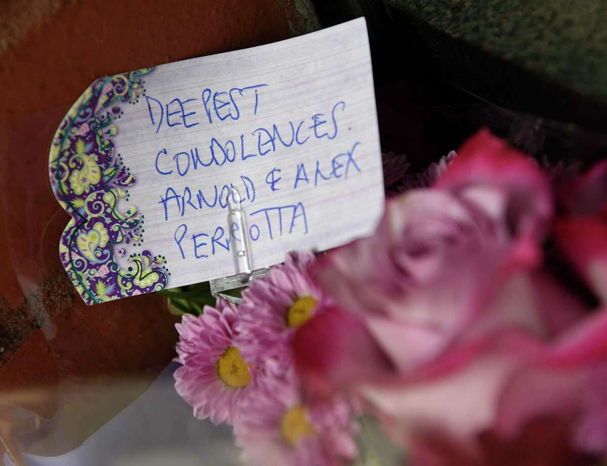 Flowers and notes sit outside Marco Jewelers in Stamford, Conn. Monday, March 30, 2020. The store's owner Mark Vuono was killed during an armed robbery at his shop on Saturday.