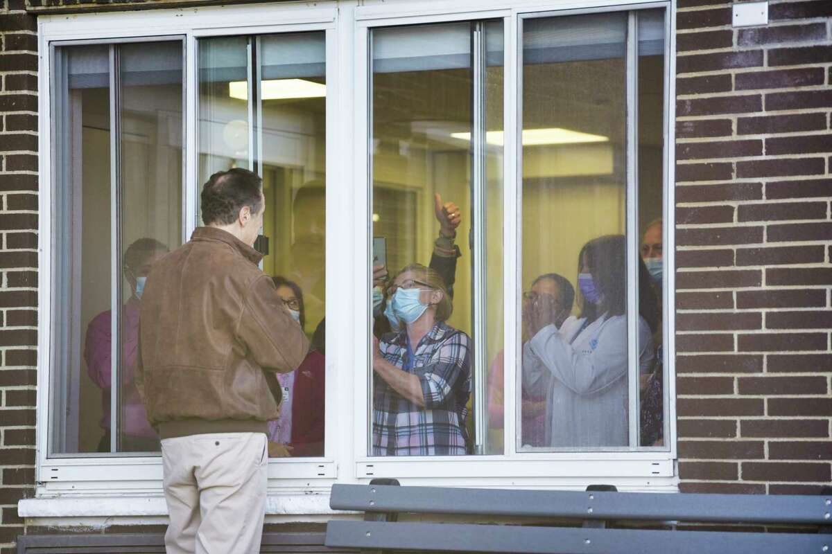 Governor Andrew Cuomo talks with staff at Pathways Nursing and Rehabilitation Center through a closed window on Sunday, April 12, 2020, in Niskayuna, N.Y. Governor Cuomo was at the center to thank them for the ventilators they loaned the state during the pandemic. (Paul Buckowski/Times Union)