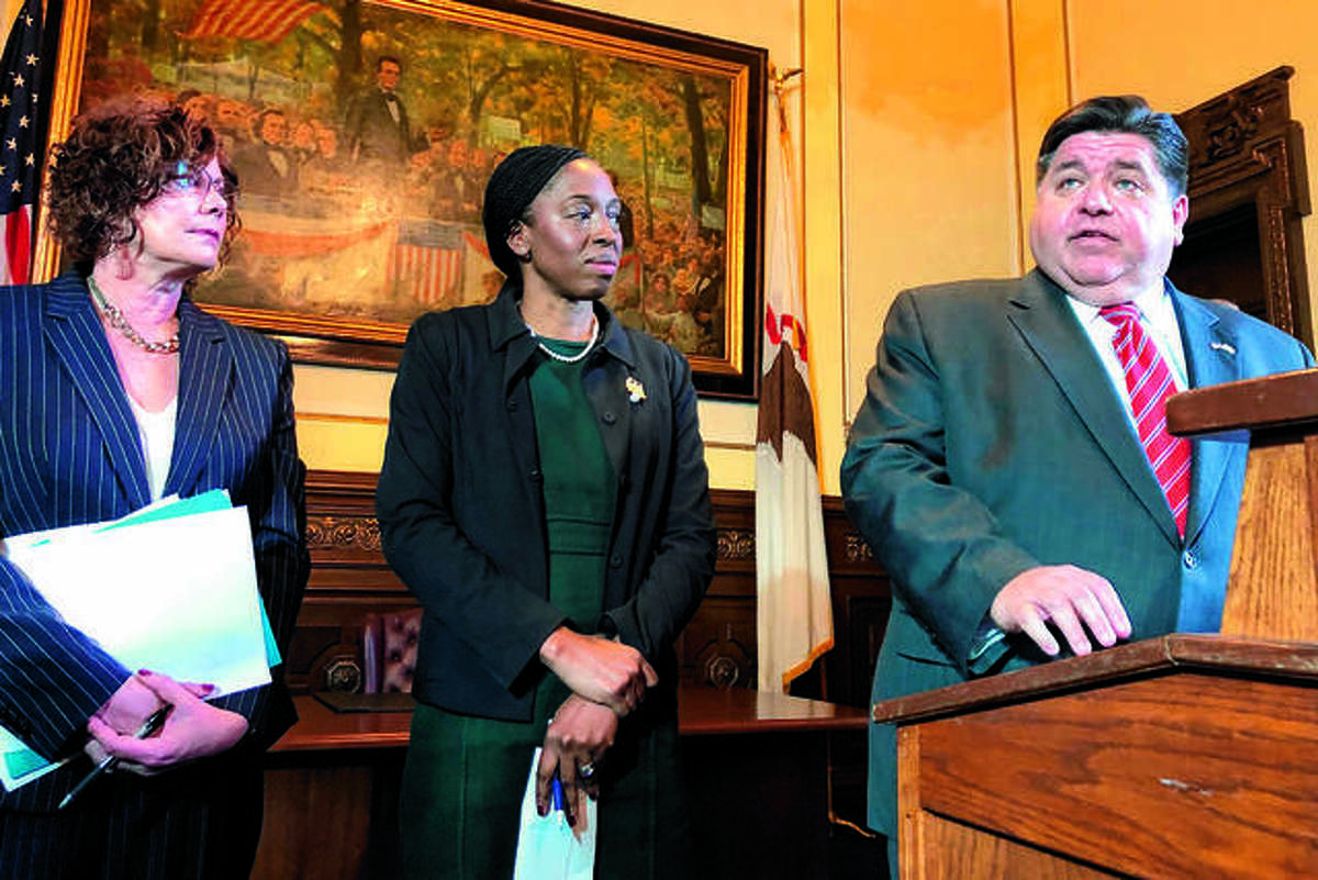 In this Hearst file photo: Illinois Emergency Management Agency Director Alicia Tate-Nadeau, left, and Dr. Ngozi Ezike, Illinois public health director, center, listen as Gov. J.B. Pritzker answers a question about the state's response to COVID-19, Thursday, March 5, 2020, at the Illinois state Capitol. (AP Photo/John O'Connor)