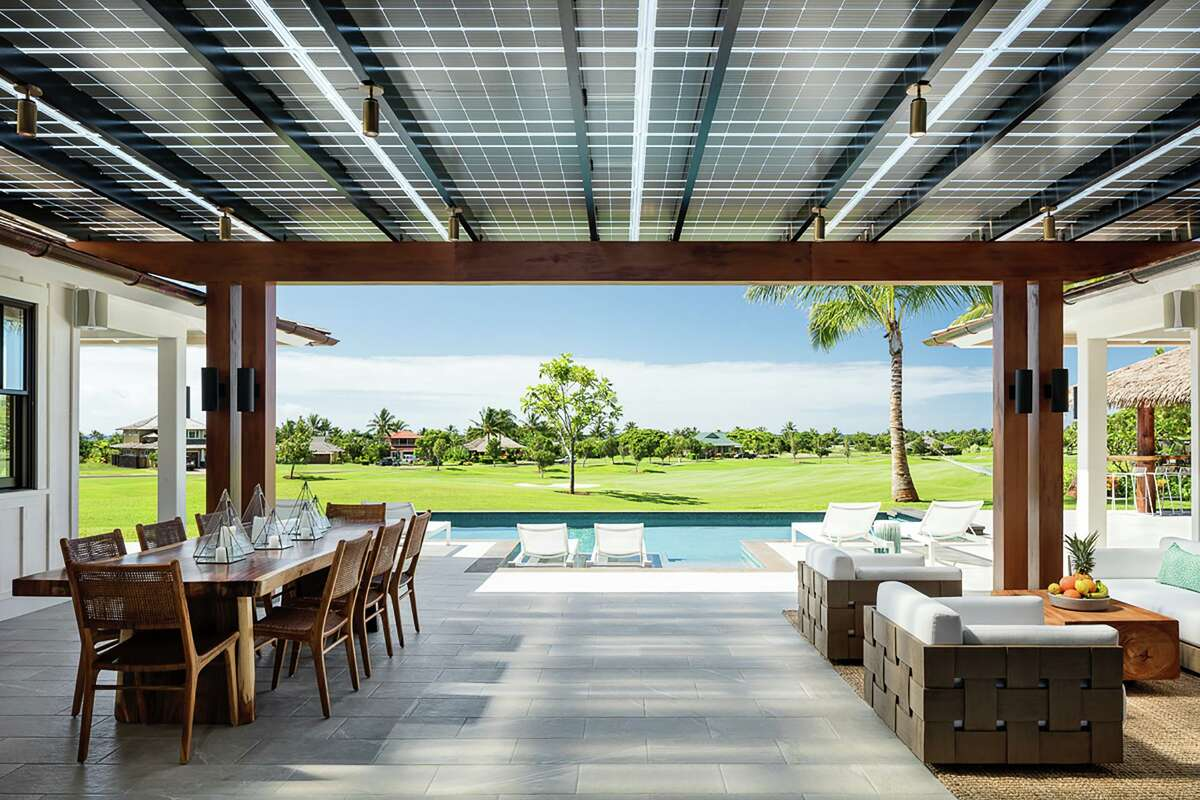 A covered lanai leads to a pool behind the modern beach house.