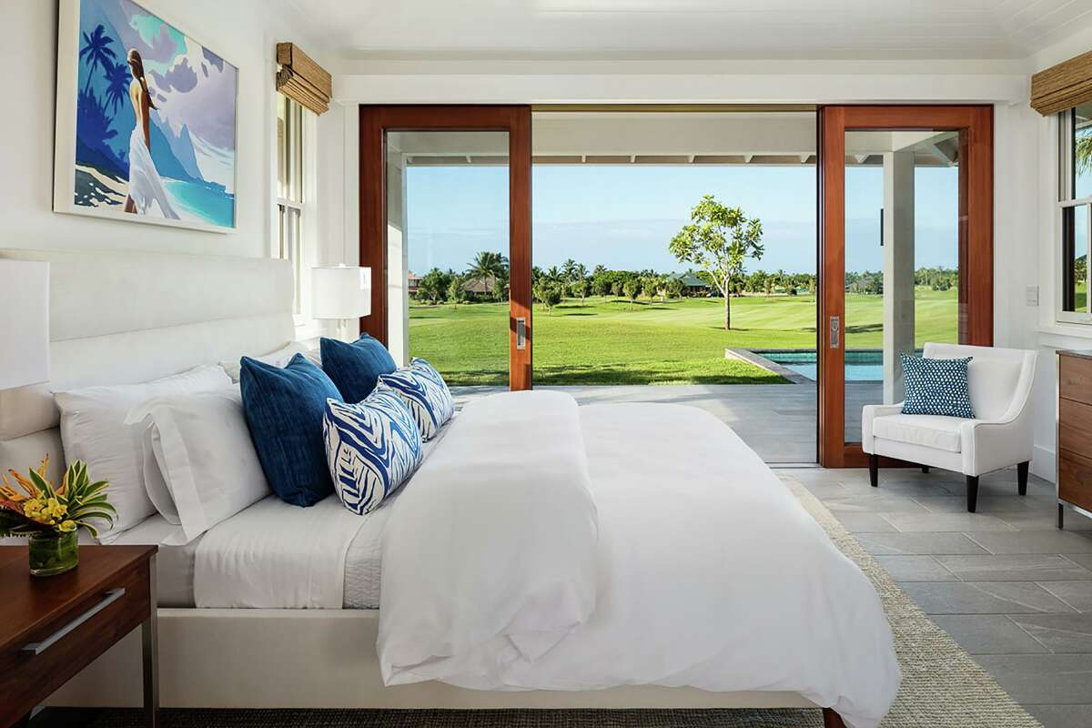 Sliding glass doors in this bedroom open to covered porch overlooking a golf course.