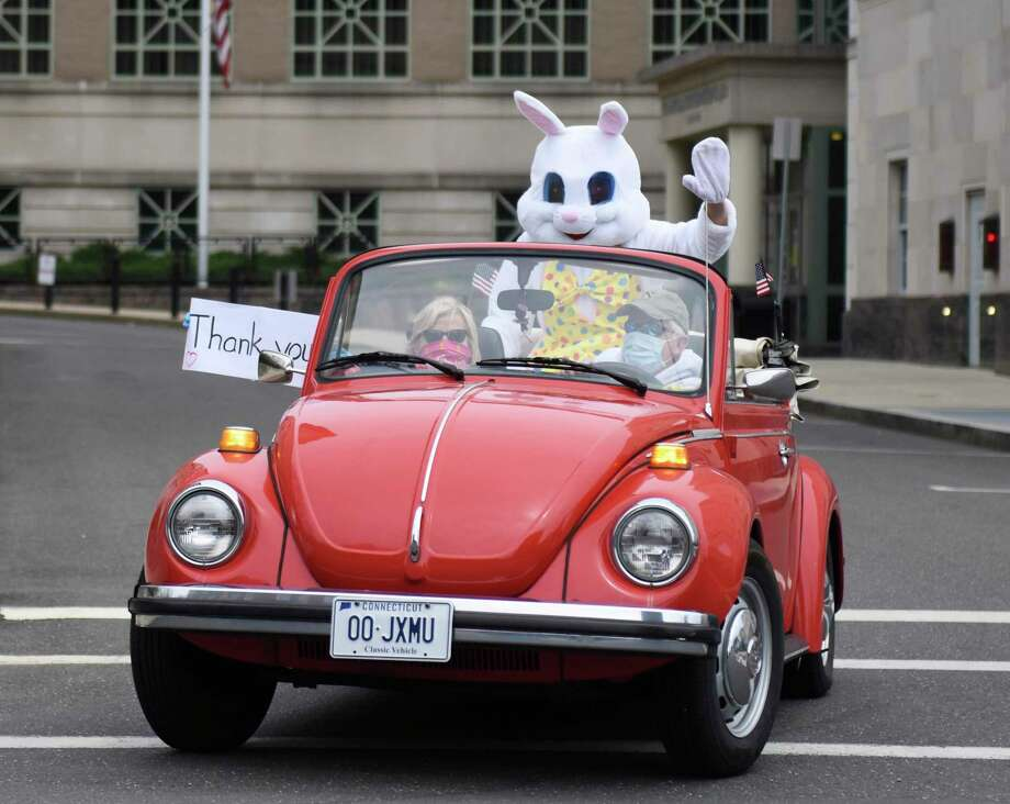 Pat and Sue Murphy, along with a man in an Easter bunny costume, drive by the Public Safety Complex to thank first responders for their dedication on Easter in Greenwich, Conn. Sunday, April 12, 2020. The Murphys also stopped at the hospital to thank medical workers and drove through downtown Greenwich to wish everybody a happy Easter. Photo: Tyler Sizemore / Hearst Connecticut Media / Greenwich Time