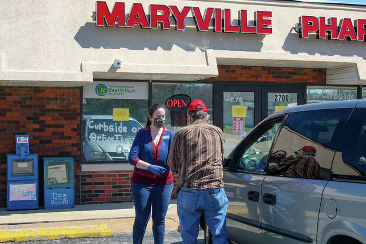 Co-owner of Maryville Pharmacy, Catherine Zollars, gives a customer their order at curbside pickup on Friday, April 10th.