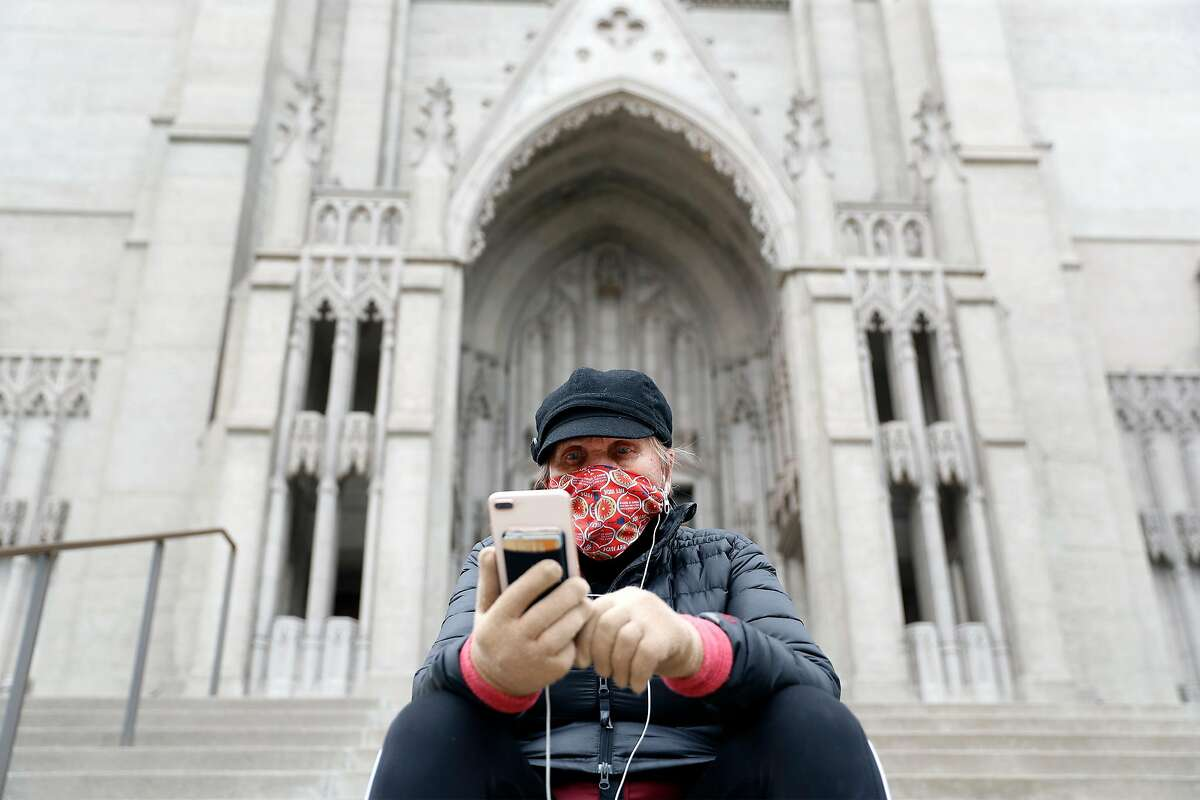 Parishioner Jude Lange watches virtual Easter Sunday service from steps of Grace Cathedral in San Francisco in April. The church will remain closed to indoor services despite a Supreme Court decision allowing them in California.