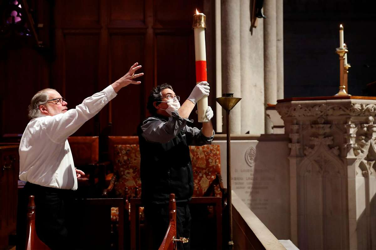 Charles Shipley (left) helps John Horton move a candle before virtual Easter Sunday service at Grace Cathedral in San Francisco, Calif., on Sunday, April 12, 2020.