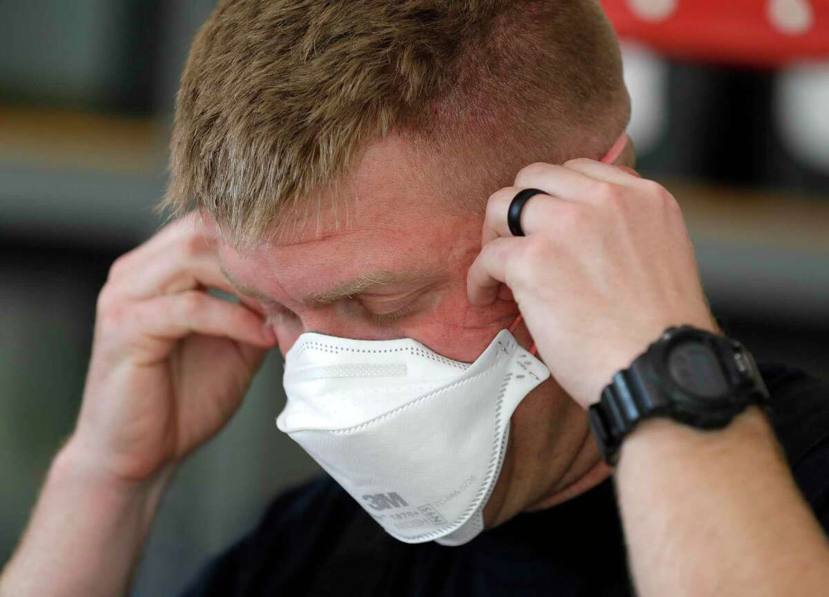 Conroe firefighter Josh Templeton checks the fit of his newly issued 3M N95 mask, Tuesday, March 31, 2020, in Conroe.