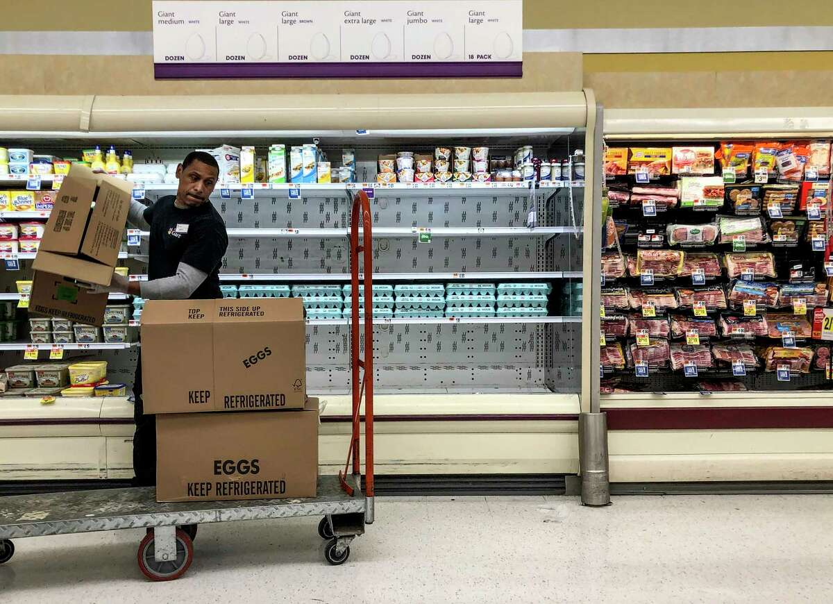 A Giant employee restocks eggs in a Silver Spring, Maryland, store Friday, March 27, 2020.