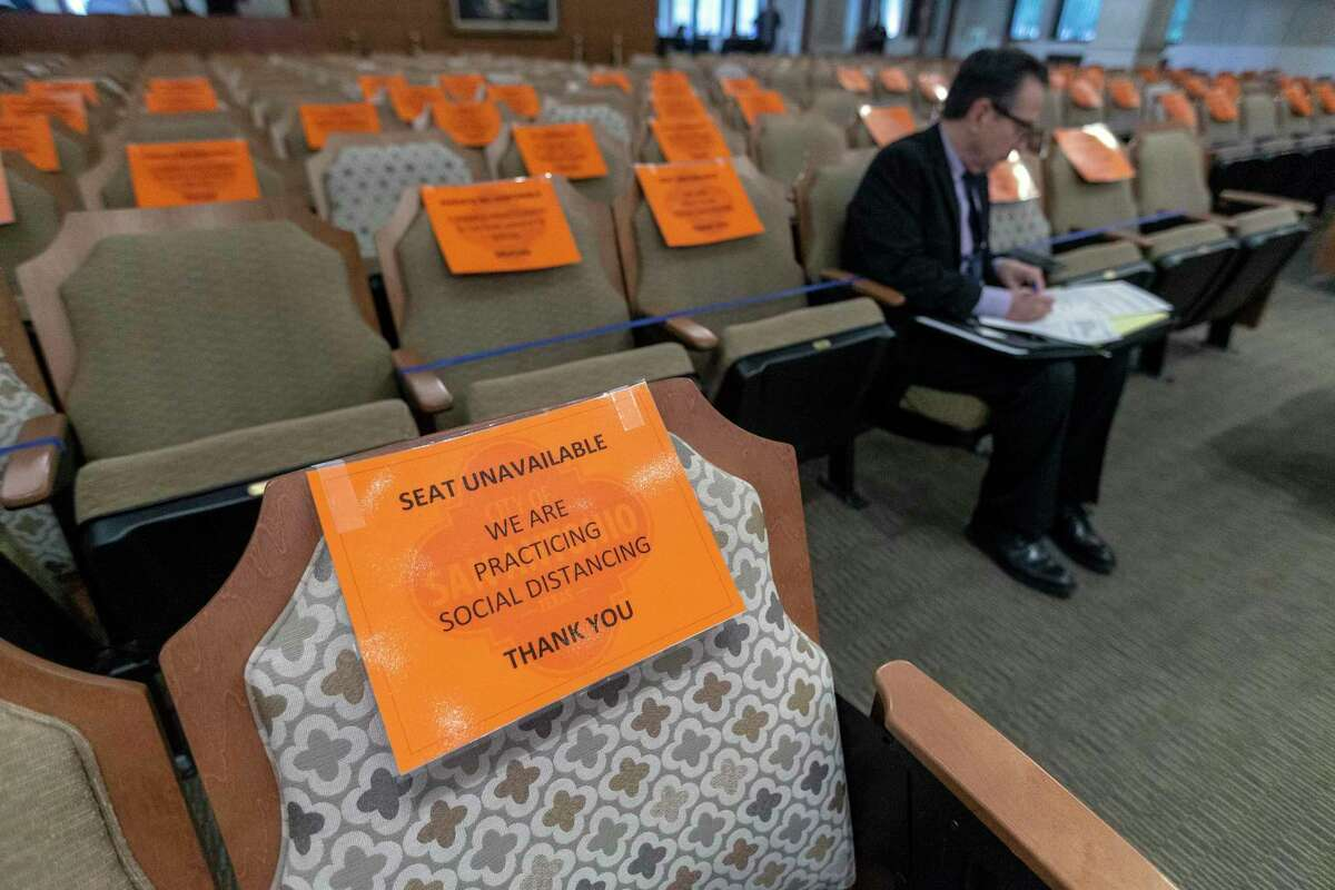 Signs indicate which seats are unavailable in San Antonio City Council chambers due to the COVID-19 coronavirus social distancing requirements. Similar signs are posted in the chambers of suburban city councils and county governments.