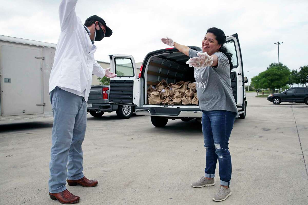"""Luciano Ciorciari gets a """"corona hug"""" from Elizabeth Lutz of the Health Collaborative as he rallies his employees at his Food Related headquarters in Schertz to assemble 400 Drop Off food deliveries on April 10, 2020."""