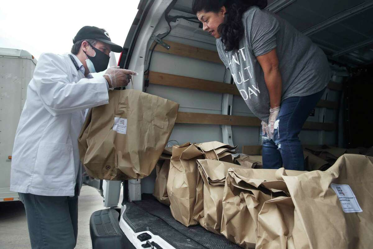 Luciano Ciorciari loads a truck for Elizabeth Lutz of the Health Collaborative as he rallies his employees at his Food Related headquarters in Schertz to assemble 400 Drop Off food deliveries on April 10, 2020.
