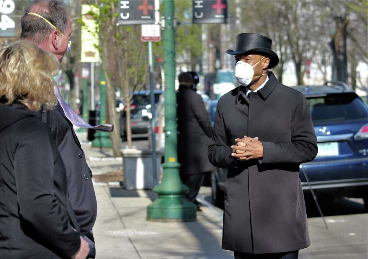 Howard K. Hill, owner of funeral homes in Bloomfield, New Haven and Hartford, at a sidewalk memorial for one of his funeral directors Saturday.