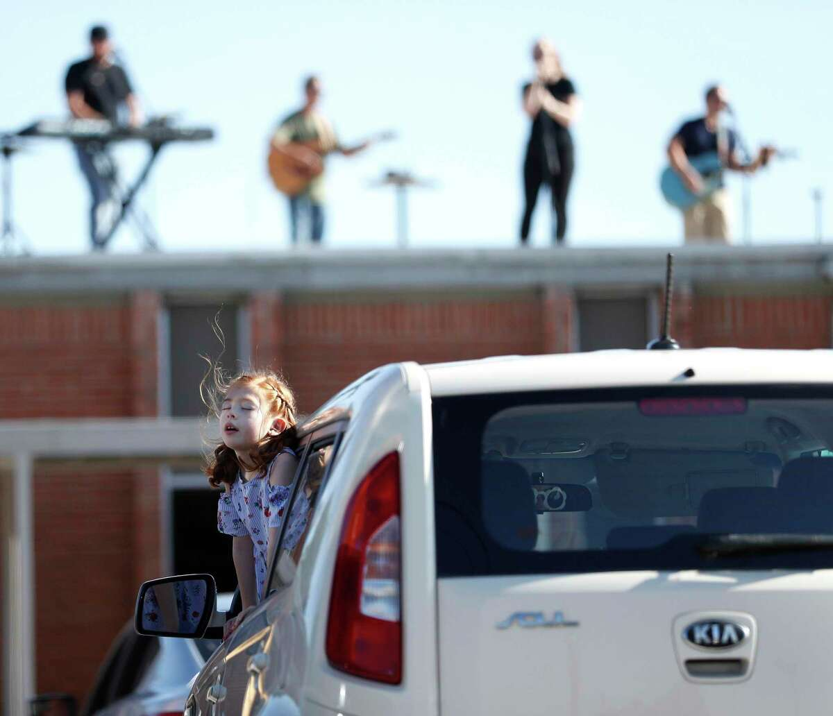 A young girl sings along with the New Day Church band as they played for parishioners in their cars from the rooftop of the church during drive-thru Easter service at New Day Church, in Houston,Sunday, April 12, 2020.