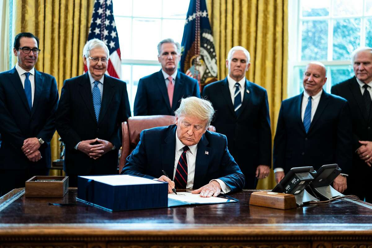 President Donald Trump signs the CARES Act at the White House in Washington, Friday, March 27, 2020. He signed into law the largest economic stimulus package in modern American history, backing a $2 trillion measure designed to respond to the coronavirus pandemic. (Erin Schaff/The New York Times)