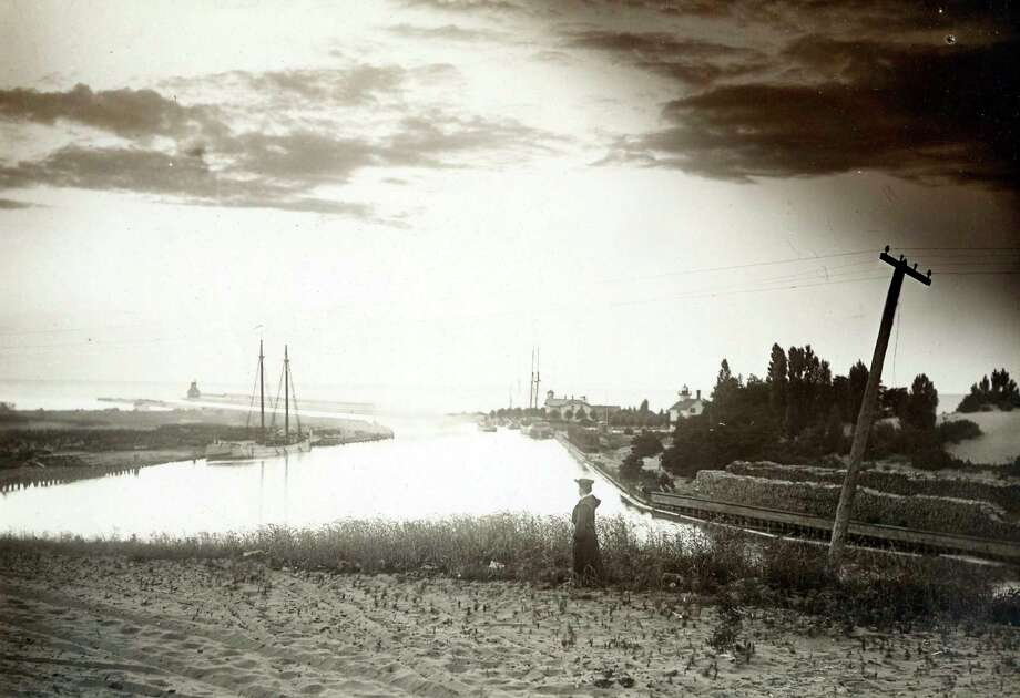 This 1890s photograph shows the Manistee Harbor at sunset with schooners lining the river channel.
