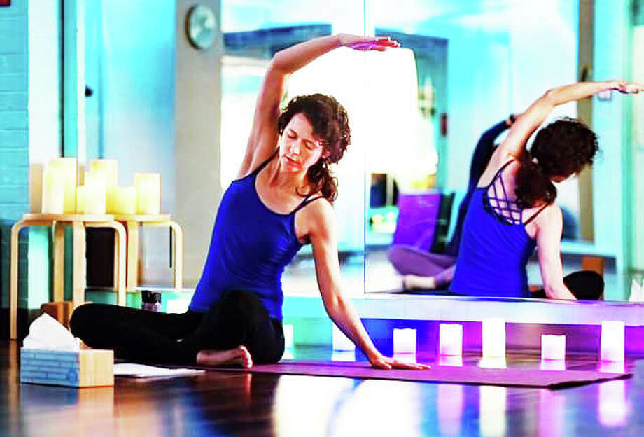 Studio Gaia Edwardsville's instructor Valerie Barber practicing yoga at the studio. Barber led the Community Exercising Together online workout April 3, day three of Edwardsville Parks and Recreation Department's new program to help citizens keep moving and inspire exercising while sheltering in place. Photo: Courtesy Of Studio Gaia Edwardsville For The Intelligencer