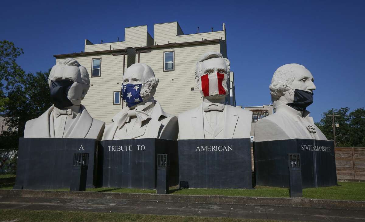 The four heads in American Statesmanship Park havePPEmasks draped over them Monday, April 13, 2020, in Houston.