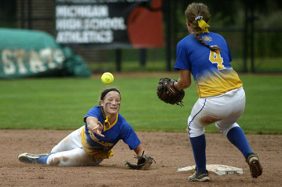 Midland High shortstop Julia Gross flips the ball to twin sister and second-baseman Tara Gross during a June 16, 2016 Division 1 semifinal vs. Macomb Dakota. Photo: Daily News File Photo