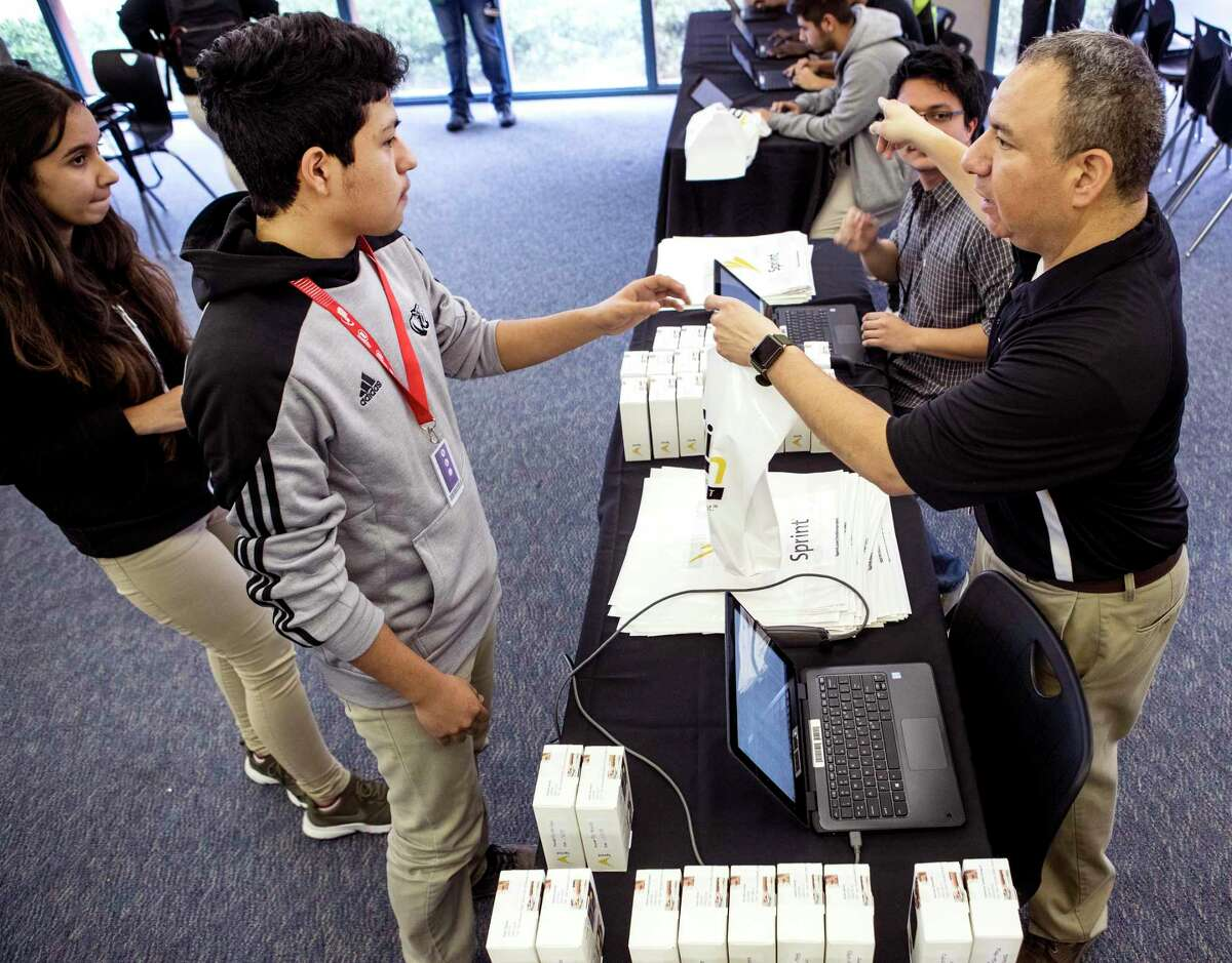 In this 2018 file photo, Jesse Martinez, left, receives his wireless internet hotspot device provided by the 1Million Project Foundation from Sam Houston Math, Science & Technology Center technology teacher Jose Ayala at the Houston ISD campus. About 21,500 district students already have a hotspot through the foundation, but more devices are needed amid the shutdown of schools due to the novel coronavirus, HISD officials said.