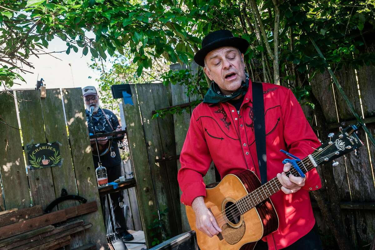 Bluegrass musicians Paul Griffiths, right, and Dave Berry, who are back fence neighbors and who often play in SF clubs, perform a Facebook live concert in San Francisco, Calif. on Friday April 10, 2020.