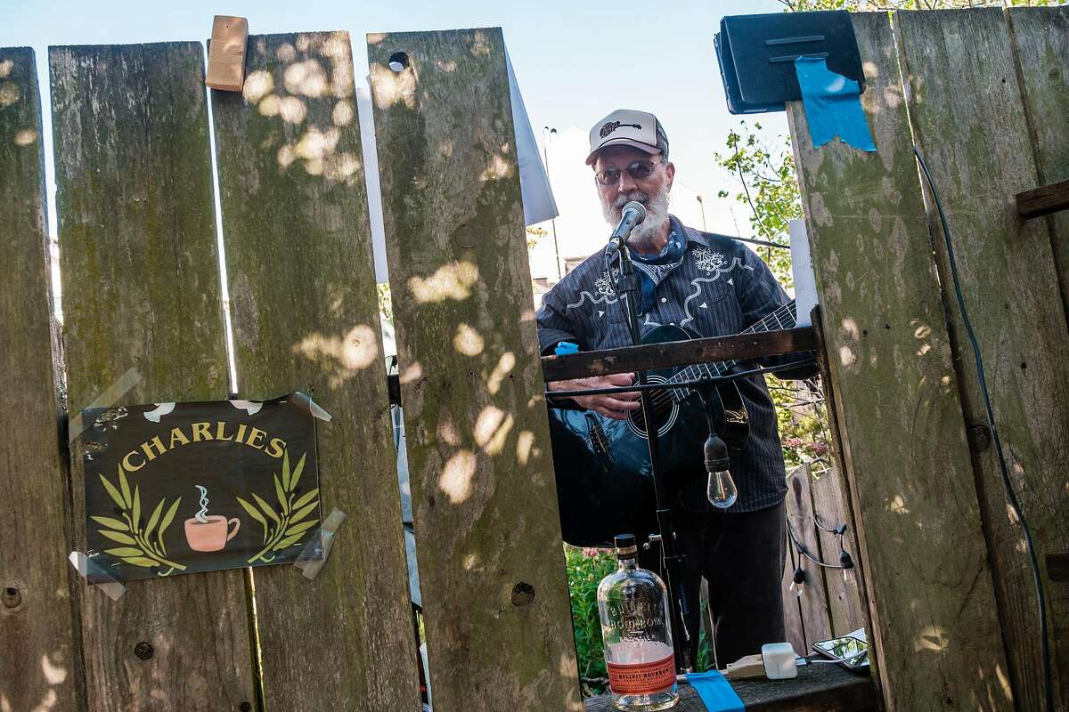 Bluegrass musician Dave Berry, sings through his fence with Paul Griffith (not seen) who are back fence neighbors and who often play in SF clubs, perform a Facebook live concert in San Francisco, Calif. on Friday April 10, 2020.