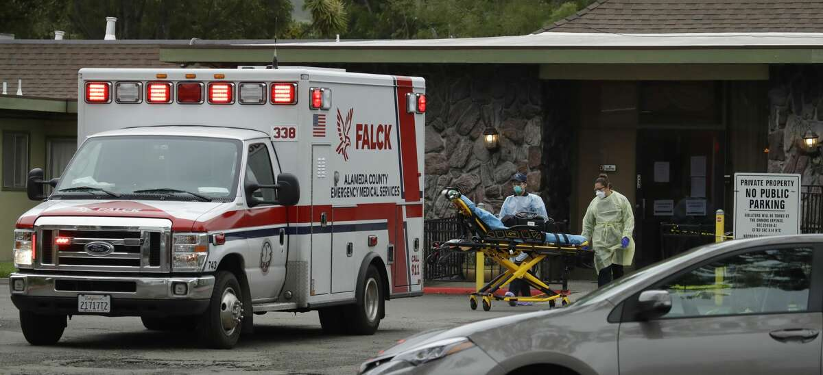 FILE: EMTs move a stretcher at the Gateway Care and Rehabilitation Center on Thursday, April 9, 2020, in Hayward, Calif.