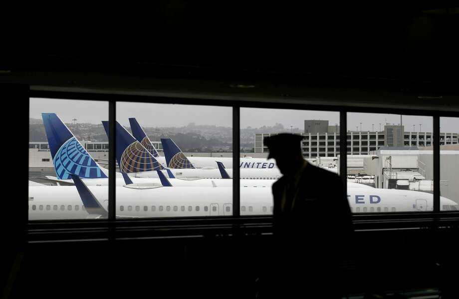 A pilot walks by United Airlines planes as they sit parked at gates at San Francisco International Airport on April 12, 2020 in San Francisco, California. San Francisco International Airport has a seen a huge decline in daily flights since the coronavirus shelter in place. United Airlines, the airport's largest carrier with the most daily flights with 290 flights per day before the start of the COVID-19 pandemic, has reduced their daily flights to 50 per day. Photo: Justin Sullivan/Getty Images / 2020 Getty Images