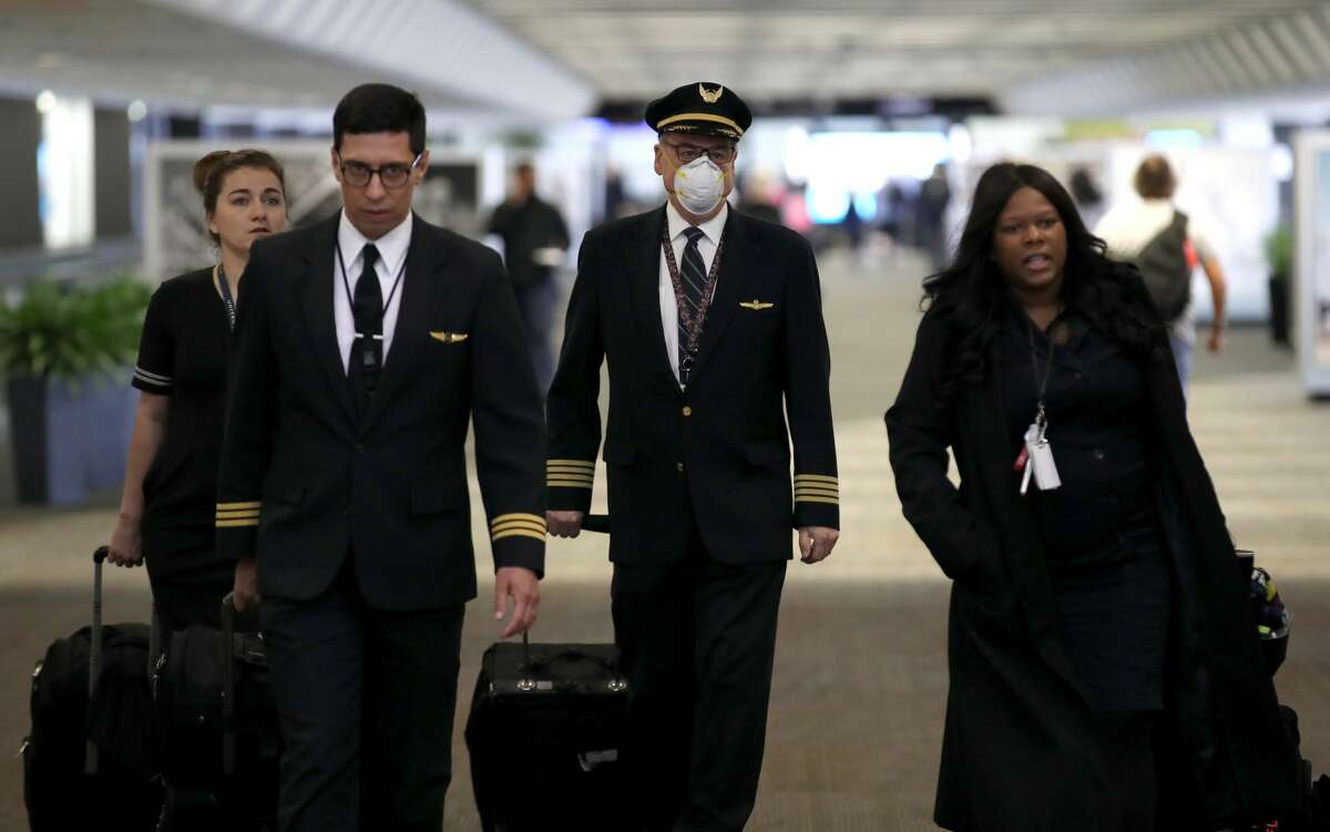 A United Airlines flight crew walks through the terminal at San Francisco International Airport on April 12, 2020 in San Francisco, California. San Francisco International Airport has a seen a huge decline in daily flights since the coronavirus shelter in place. United Airlines, the airport's largest carrier with the most daily flights with 290 flights per day before the start of the COVID-19 pandemic, has reduced their daily flights to 50 per day.