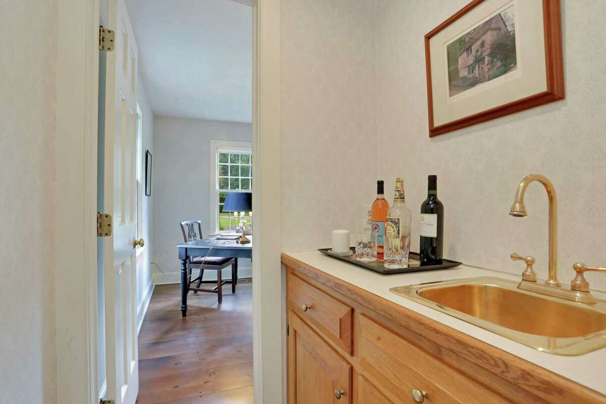 Between the living room and office there is a wet bar with a brass sink.