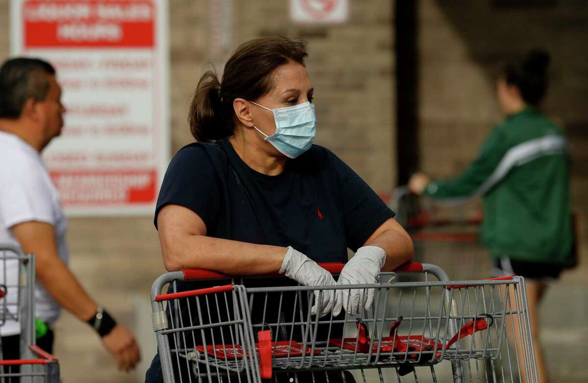 A woman wears a face mask and gloves as she waits to enter the Costco Wholesale at Bunker Hill Road in March. Health officials in Houston noted that the COVID-19 curve had begun to flatten, seen in testing and hospitalization data. It could represent the turning of a significant corner for an area that has been shut down for more than a month to curb the spread of the coronavirus that causes COVID-19.