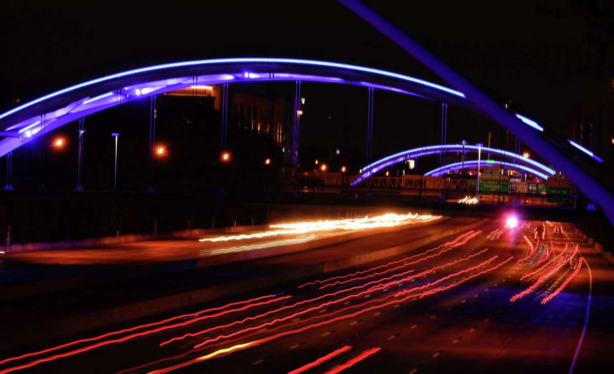 Traffic moves along Interstate 69 under blue lighted bridges shown from the Dunlavy bridge on April 9, 2020.