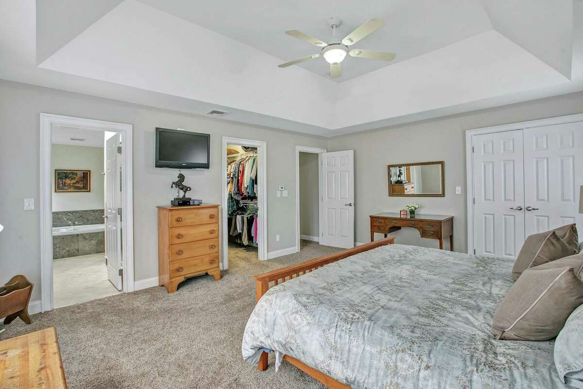 The sizable master suite features a deep tray ceiling, a ceiling fan, walk-in closet, a second closet, and a private bath.