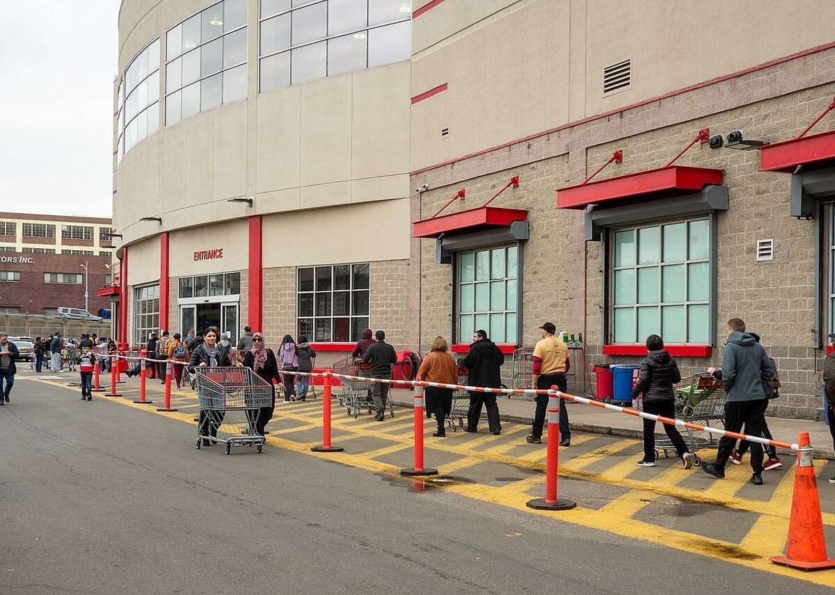 Shoppers maintain physical distancing while queuing up outside a Costco store during the coronavirus pandemic.