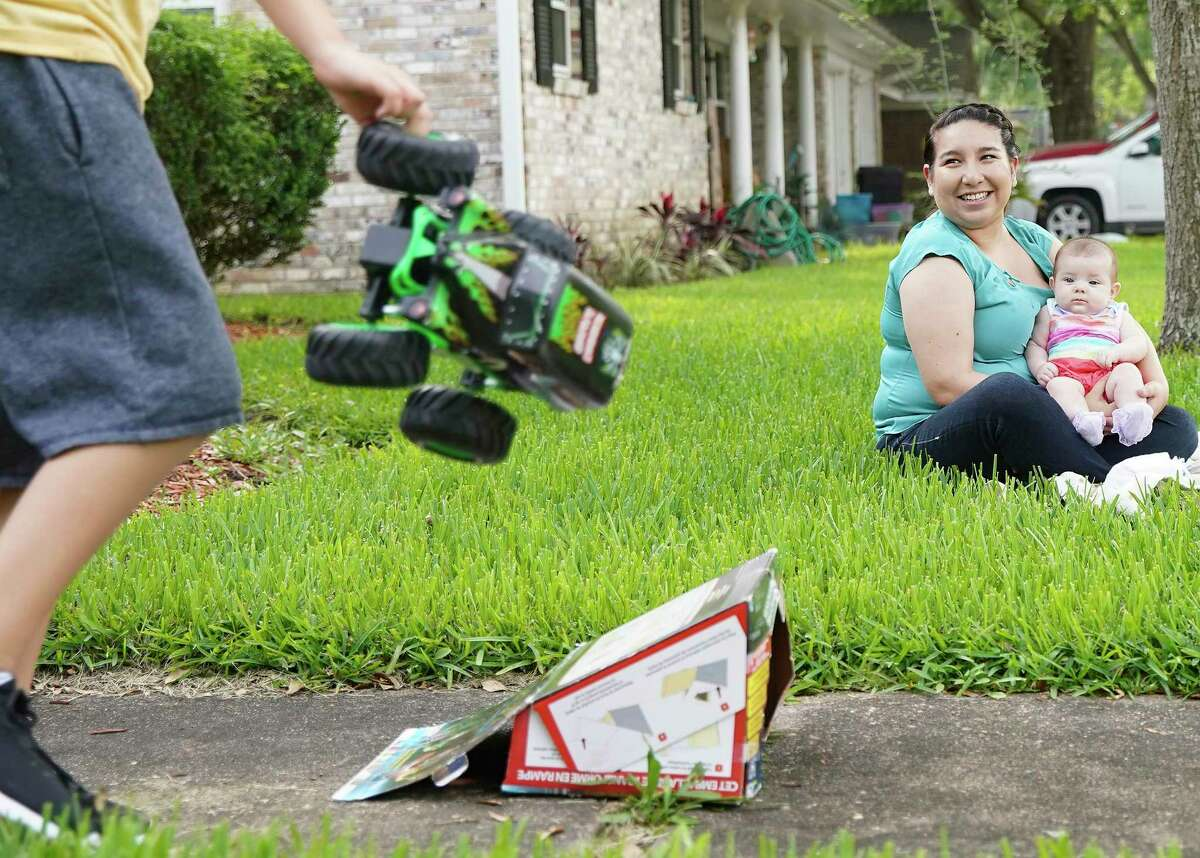 Bianca Huerta outside her home with her 4-month-old daughter, Everley, and son Andrew, 11, in Dickinson.