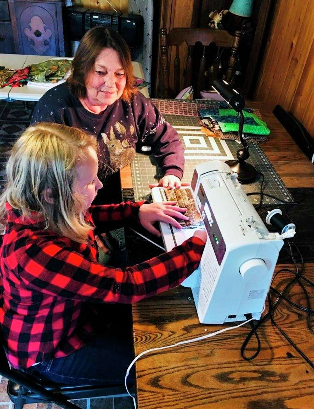 """Ten-year-old Paris resident Lily Modene received her first sewing machine from her grandmother, """"Grandma Julie,"""" and was taught how to sew. Featured are the two of them as Modene creates a mask for a local in need. (Courtesy)"""