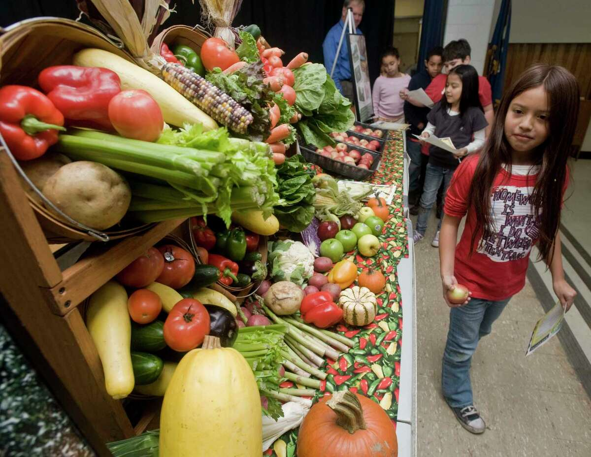 Arazely Urvina, a third-grader at Morris Street School, looks over a display of fruit and vegetables in the cafeteria in 2010.