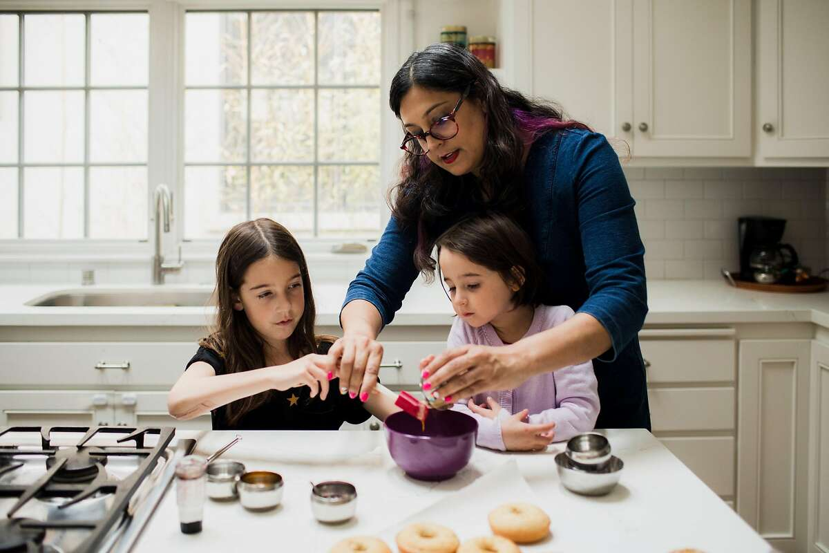 Writer Leena Trivedi-Grenier makes mango cardamom donuts with her daughters, Remy and Ella, in their kitchen on March 5, 2020 in Oakland, California.