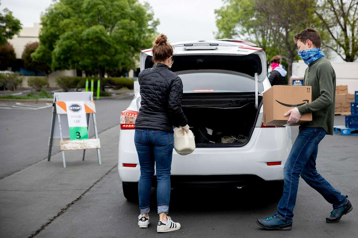 Volunteers work together to distribute food boxes and gallons of milk to residents in need at the San Francisco-Marin Food Bank in San Rafael, Calif. Saturday, April 11, 2020. San Francisco-Marin Food Bank has set up several new distribution centers, including this drive-through one in San Rafael where residents pull up, pop their trunks and have the goods dropped in.